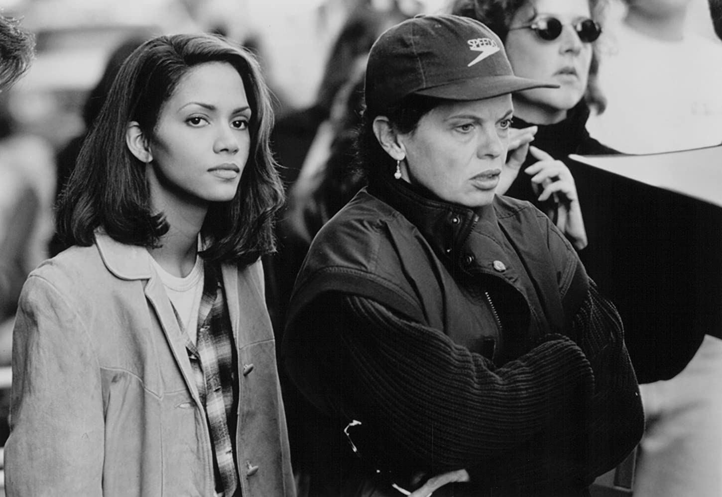 A black and white image of Halle Berry and Amy Holden Jones on the set of The Rich Man's Wife in 1996. Holden Jones, right, a white woman around 40, wears a thick dark sweater and a gilet over it, and a dark Speedo baseball cap. She has her arms folded and is intently watching something out of the frame. The actress, Berry, a Black woman around 30, stands beside Holden Jones, wearing a pale trench coat over a buttoned up plaid shirt. She is also gazing off-camera.