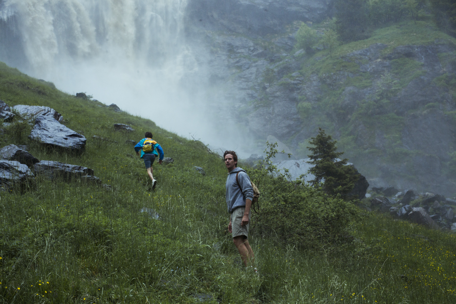 Armie Hammer and Timothée Chalamet in Call Me by Your Name (2017). A vast hillside in Italy with a rushing waterfall in the background, Elio, a teenage boy wearing a blue raincoat and a yellow backpack, heads off towards the waterfall. In the foreground is his companion, the older Oliver, wearing a grey hoodie and shorts, looks back towards the camera.