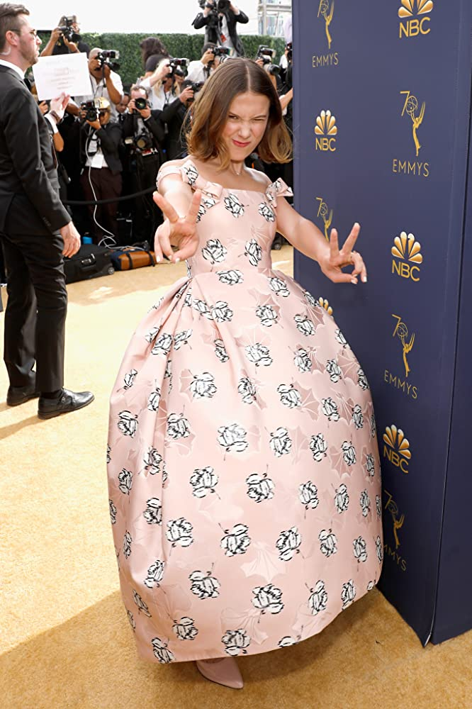 Millie Bobby Brown en robe de soirée rose bouffante à motif florale à épaule dénudée aux Emmy Awards 2018