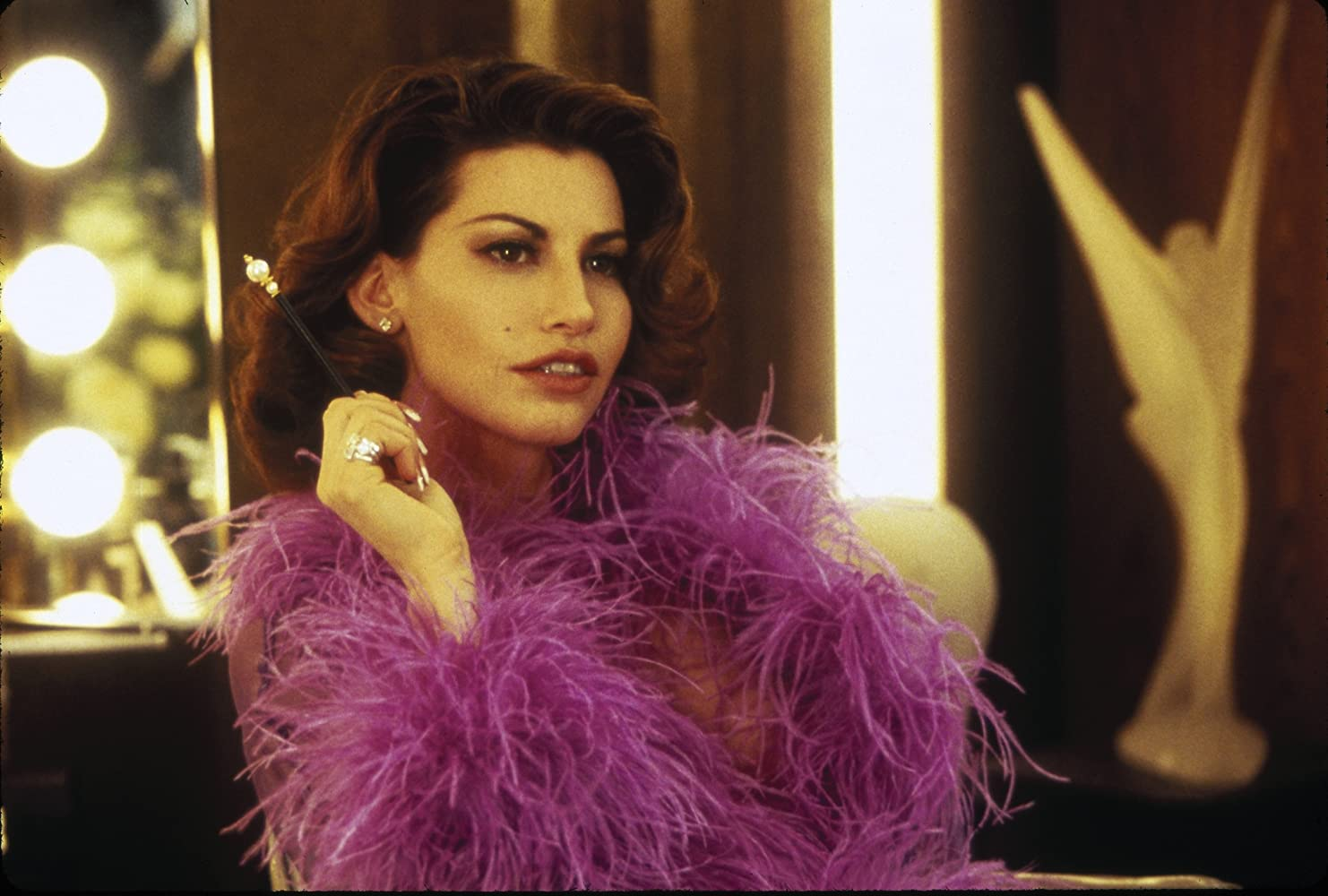 Showgirls (1995). Cristal, a brunette white woman in her early thirties, reclines on a chair in the dressing room, a cigarette holder in her hand. She wears a feathery purple top and has immaculate makeup. She looks intrigued, regarding something out of the frame.