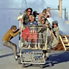 """(left) Dave England, (right) Ehren McGhehey, (in shopping cart, beginning center clockwise) Jason """"Wee Man"""" Acuna, Bam Margera, Ryan Dunn, Steve-O, Chris Pontius, and Johnny Knoxville."""