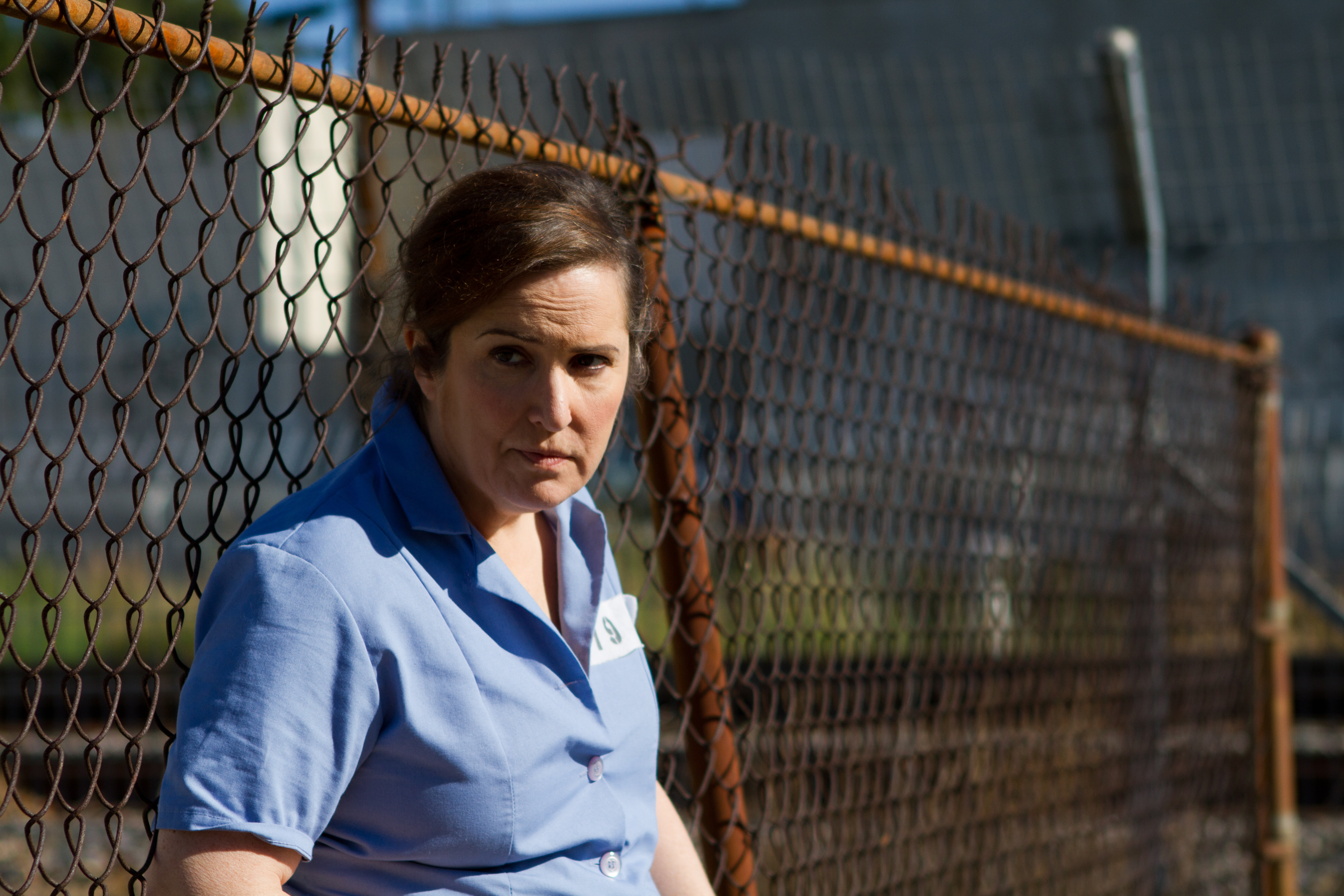 Actress/Director Jillian Armenate leans against the prison yard fence for Kittens in a Cage.