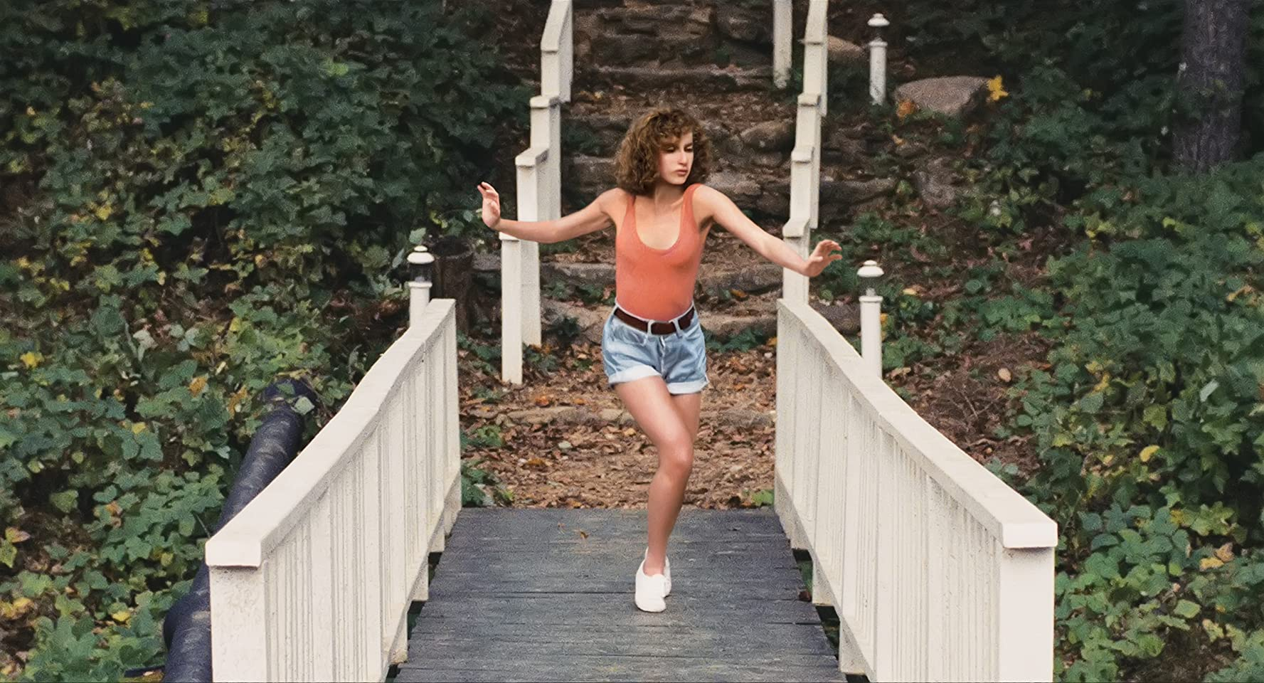 Jennifer Grey in Dirty Dancing (1987). Baby, a young white woman with very curly brown hair, is dancing her way along a small wooden bridge amongst the foliage. She is wearing a salmon coloured vest, blue denim shorts, and white plimsolls.