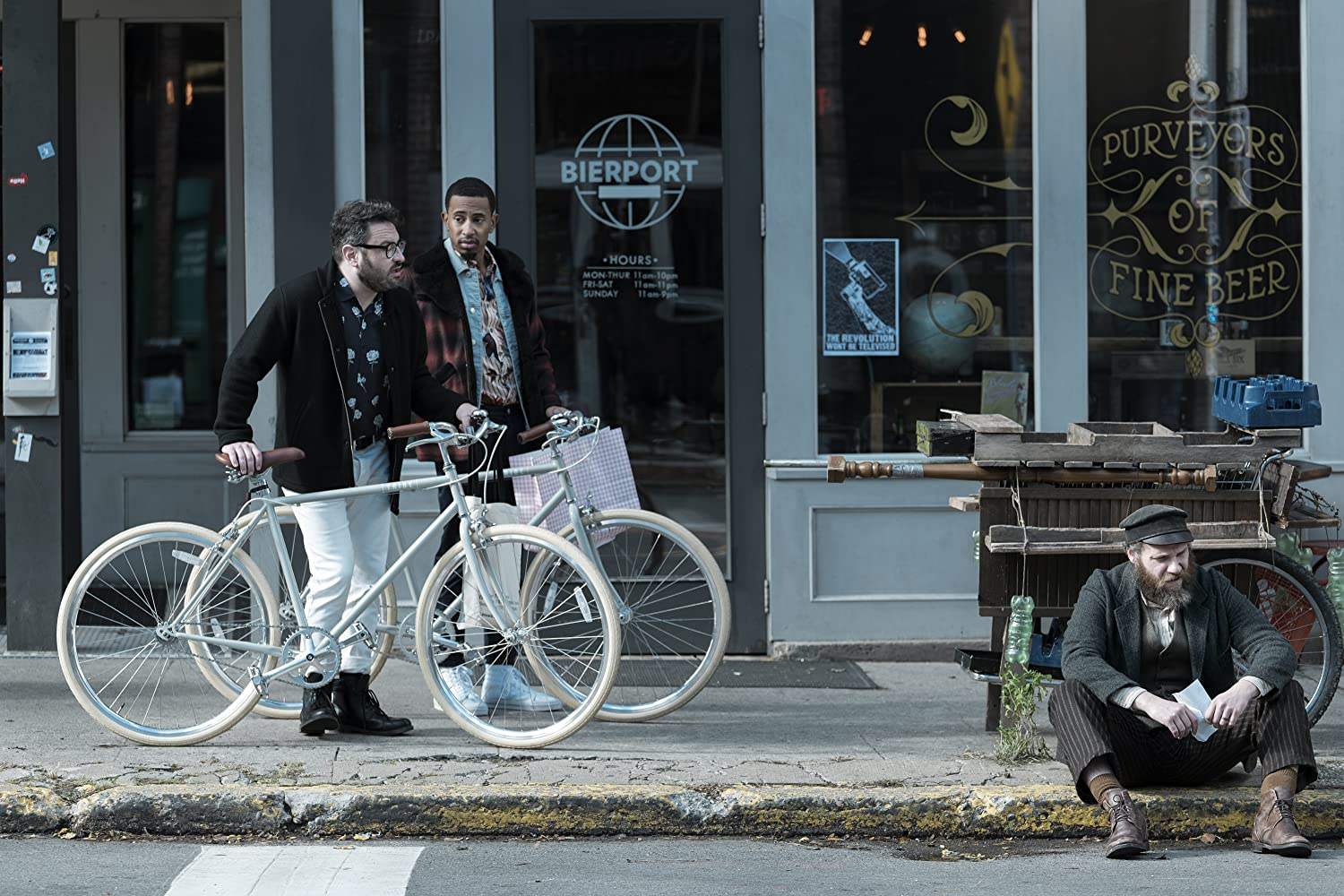 Seth Rogen, Eliot Glazer, and Kalen Allen in An American Pickle (2020). A New York street during the day, in front of a bar. Christian (Glazer) and Kevin (Allen) are stood with matching pale blue bicycles, smartly dressed in modern clothes. They are looking incredulously at Herschel (Rogen), a Jewish man with a thick beard and clothes 100 years out of date, who is sitting on the curb holding a sheet of paper and looking dejected.