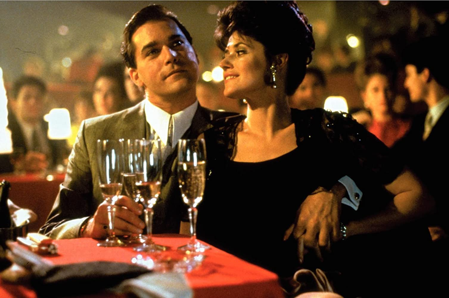 Ray Liotta and Lorraine Bracco in Goodfellas (1990). Henry and Karen Hill are at a dimly lit bar, sitting at a small table with four glasses of champagne sitting in front of them. Karen sits closely to her husband, who has his arm wrapped around her waist and clenches her hand, either protective or possessive. Henry, in a grey suit, is watching off-camera but Karen looks at him, her short dark hair is in a bouffant style and she wears glamorous makeup and gold earrings as well as a fitted black dress.