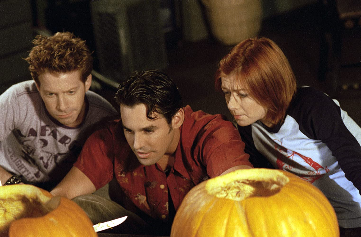 Seth Green, Alyson Hannigan, and Nicholas Brendon in Buffy the Vampire Slayer (1997). L-R Oz, Xander, and Willow are crouching behind some pumpkins with the tops cut off and the guts scooped out. Oz is a white man with spiky light brown hair and a brown graphic tee on, whilst Xander has slicked back dark brown hair and a red button-up shirt on, holding a knife. Willow has short red hair and a black and white baseball top on. They are all staring at the pumpkin in front of them.