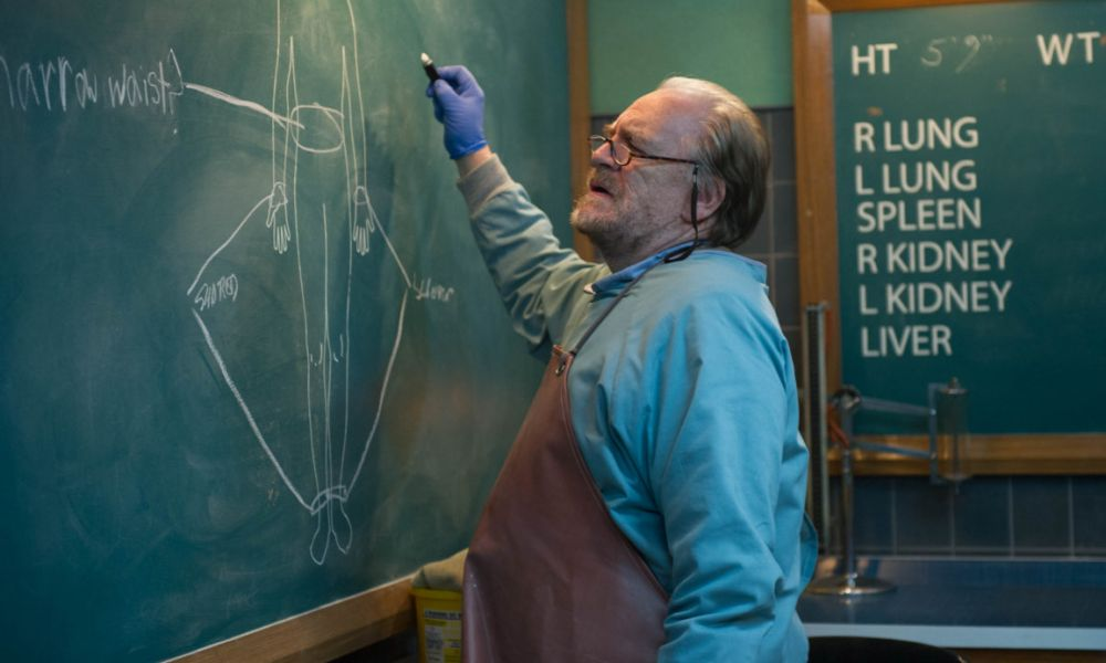 "The Autopsy of Jane Doe (2016). Tommy, a mortician who looks to be in his 60s with thinning grey hair and a scruff of beard, poises to write something on a large chalk board diagram of a woman's body. He is wearing blue protective clothing, surgical gloves, and a brown apron. Behind him, a second board lists: ""R Lung, L Lung, Spleen, R Kidney, L Kidney, Liver"""