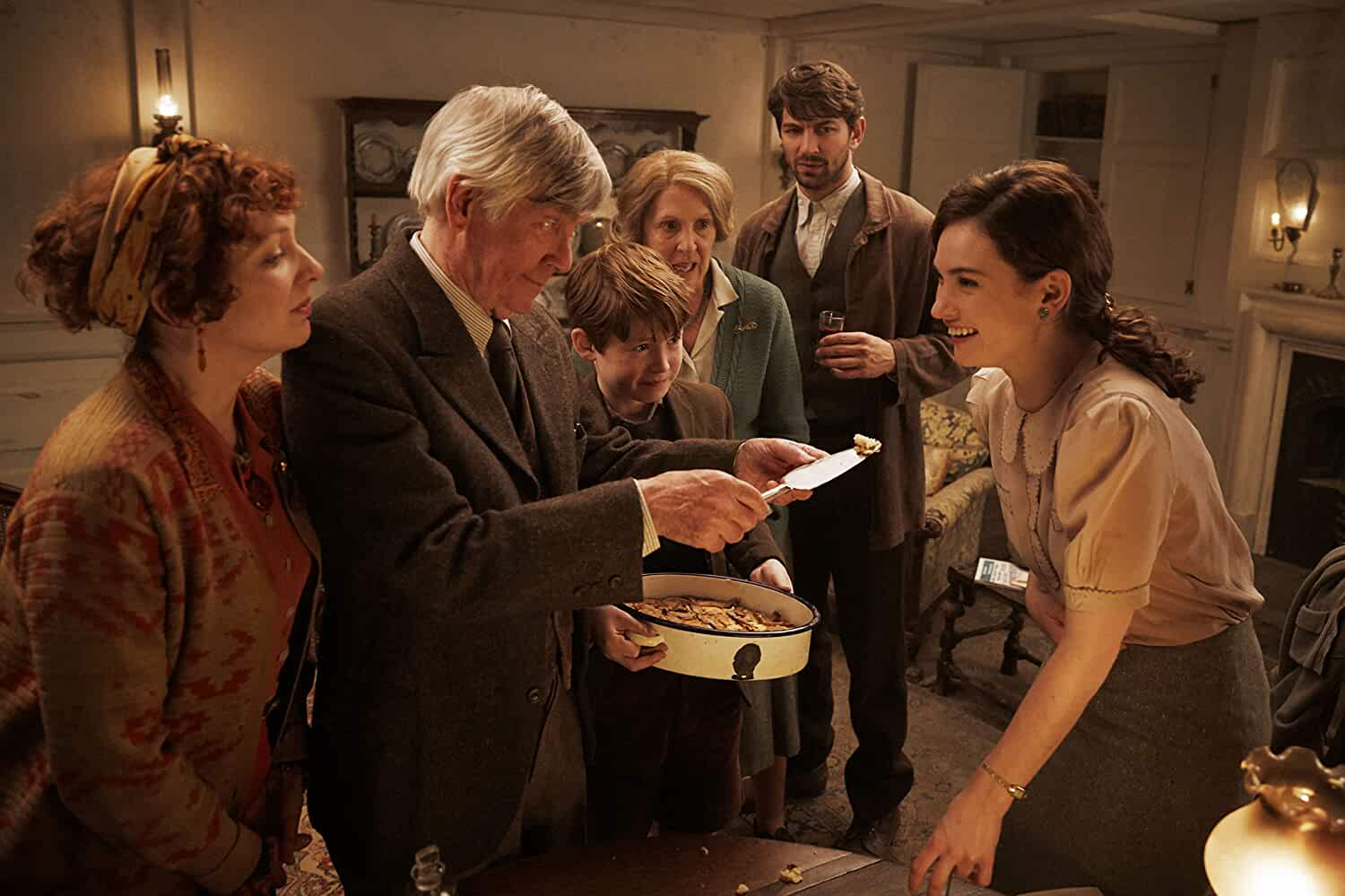 Tom Courtenay, Michiel Huisman, Penelope Wilton, Katherine Parkinson, Lily James, and Kit Connor in The Guernsey Literary and Potato Peel Pie Society (2018)