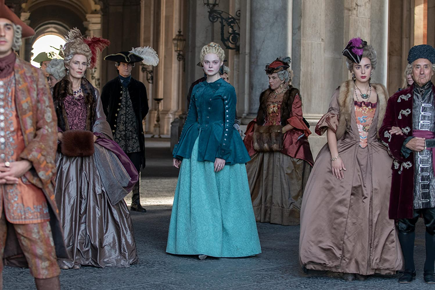 Elle Fanning in 'The Great' (2020). Catherine, her hair pulled back in an updo, is wearing a light turquoise gown with a darker teal velvet jacket over the top which buttons up to her neck in a more austere look. She stands centre frame in a crowd of other courtiers wearing elegant gowns and suits, but all in shades of brown and orange, making Catherine stand out.