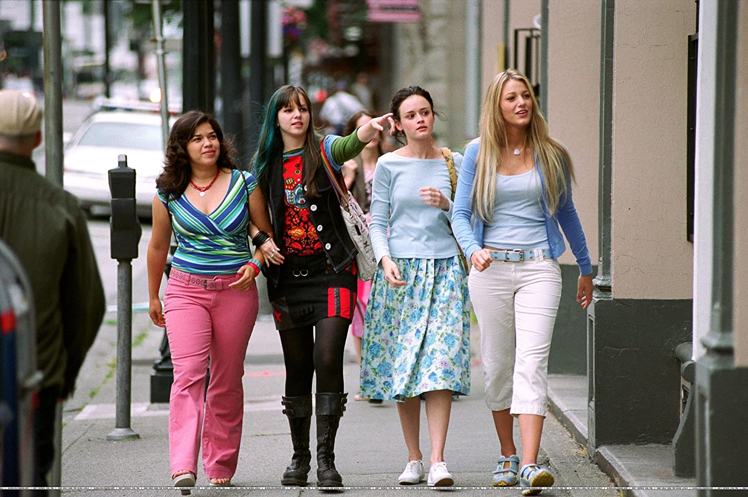 Alexis Bledel, Blake Lively, Amber Tamblyn, and America Ferrera in The Sisterhood of the Traveling Pants (2005). Four female friends, Carmen, Tibby, Lena, and Bridget, are walking along a city street during the day, dressed in colourful girly outfits - except for Tibby, who has long hair dyed blue and wears a black and red goth-style outfit. Tibby is pointing to something further along the street, the other girls look on with curiosity.