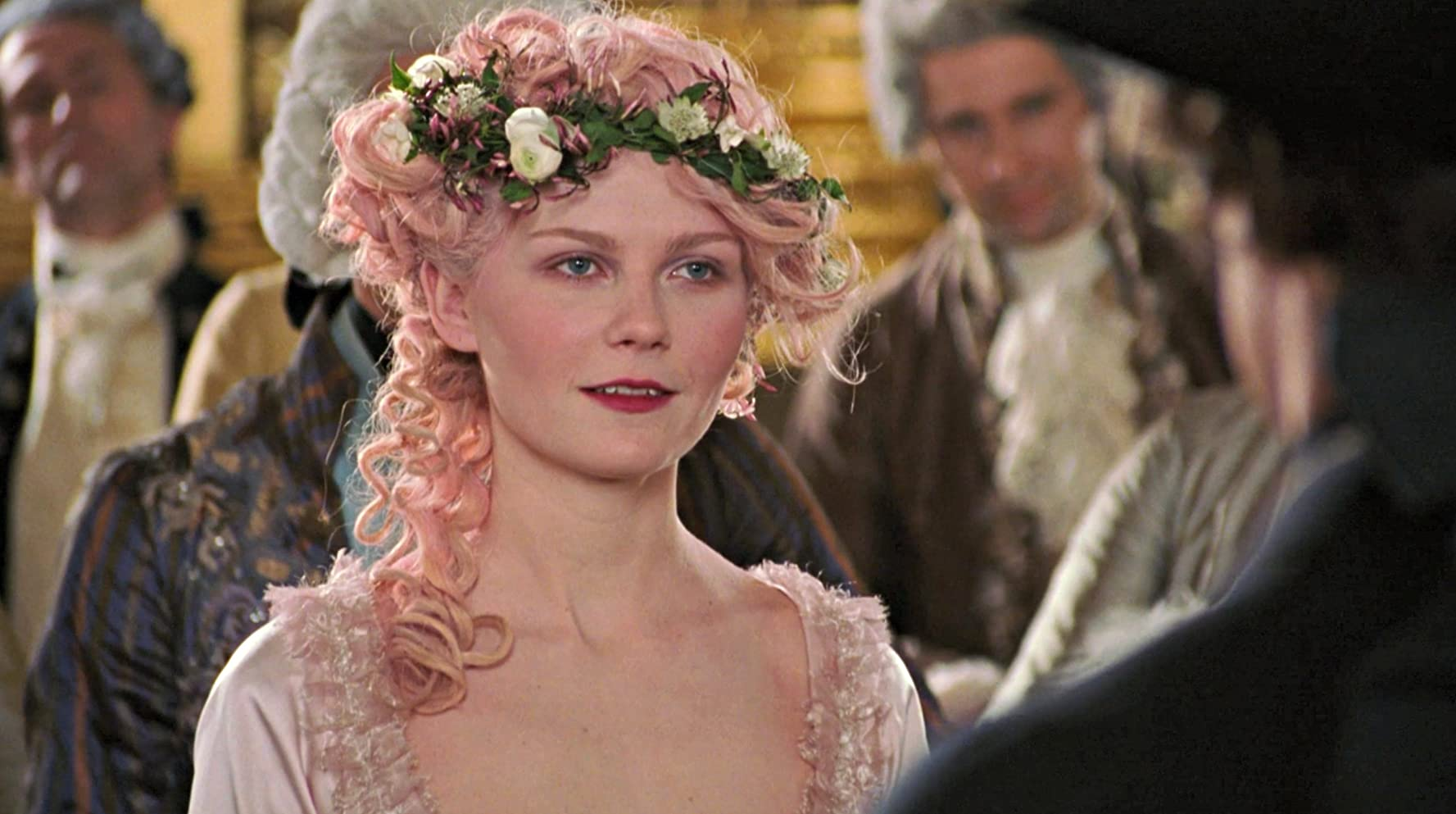 Kirsten Dunst in Marie Antoinette (2006). A close up of Marie, dressed in a pale pink satin gown and her wig a matching dusty pink colour, adorned with a white flower wreath.