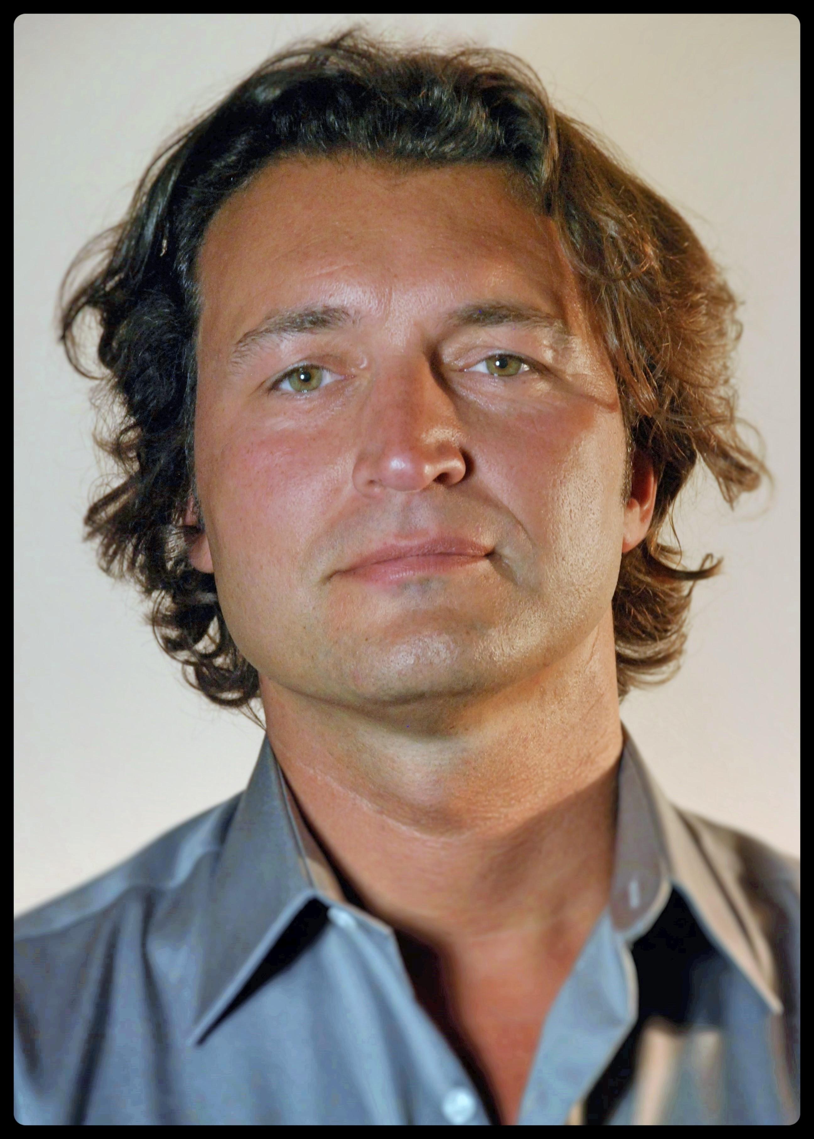 Karl Farrer professional headshot. Long hair