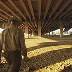 Rancher Henry Brooks traverses a barren landscape beneath a highway overpass