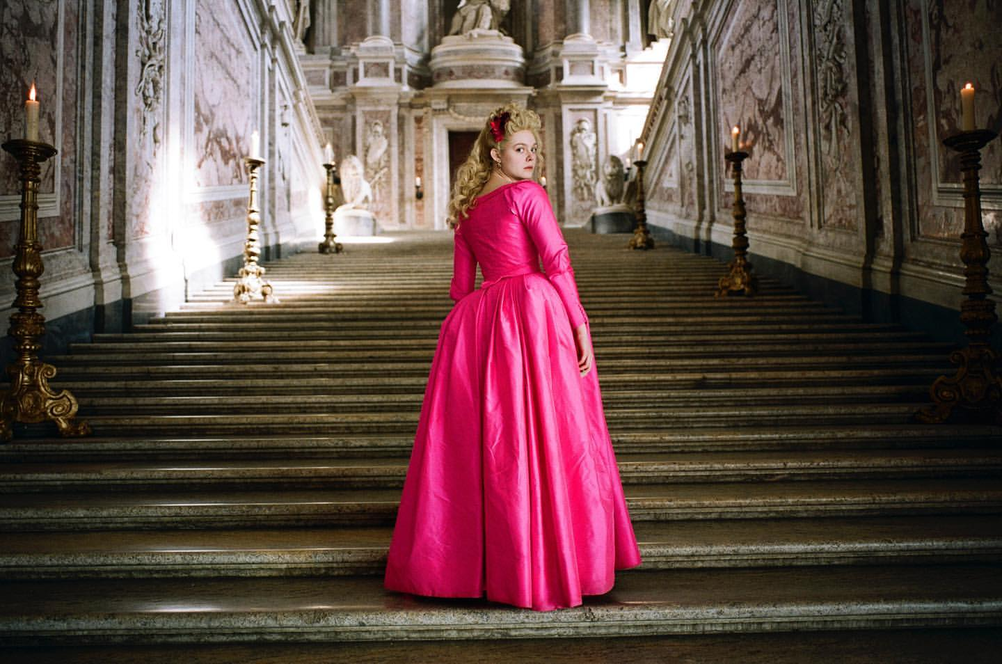 Elle Fanning in The Great (2020). Catherine, the young princess, is standing on an ornate palace stairway, her body facing away but her head turned to look at the camera. Her pale blonde hair is curled in a half updo, and she wears a hot magenta satin gown that reaches the floor.