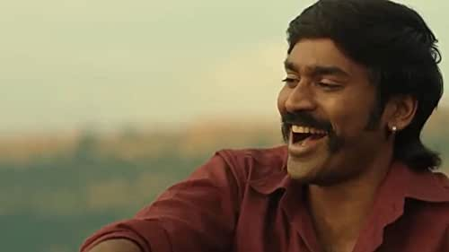 """""""Suruli"""" (Dhanush) is a reckless, gangster from Madurai who happens to get recruited by a London-based politically-affluent gang leader 'Peter' (James Cosmo) and his men to understand and break into the illegal underworld operations of the 'Sivadoss' (Joseph 'Joju' George) and his gang which is rising in power, taking control of the illegal weapons and gold business of London. The fundamental theme of """"Suruli"""" is about a fight for what you can truly call home seen from the perspectives of three different characters."""