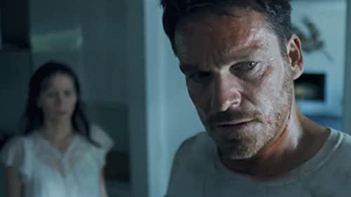 In HELD, Emma (Jill Awbrey) and Henry's (Bart Johnson) marriage is losing its spark. In an effort to reconnect, they vacation to a remote high-end rental, complete with automated smart house features and integrated security. However, after suspecting a nighttime intruder they decide to flee, only to become forcibly trapped inside by the automated security system. Emitting from the house, an unknown 'Voice' watches their every move through an array of hidden cameras, revealing an intimate and unsettling knowledge of their relationship. While the situation grows increasingly brutal, Emma and Henry must work together to uncover the truth and find a way out before it's too late.