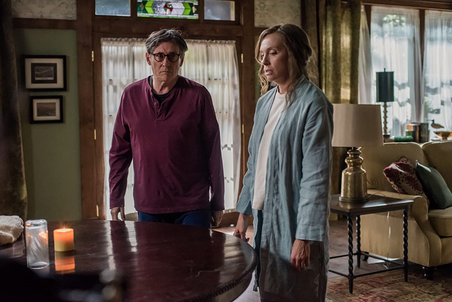 Annie and her husband in Hereditary (2018). The pair look solemn together.