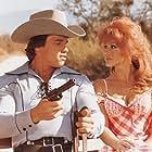 Arnold Schwarzenegger and Ann-Margret in The Villain (1979)