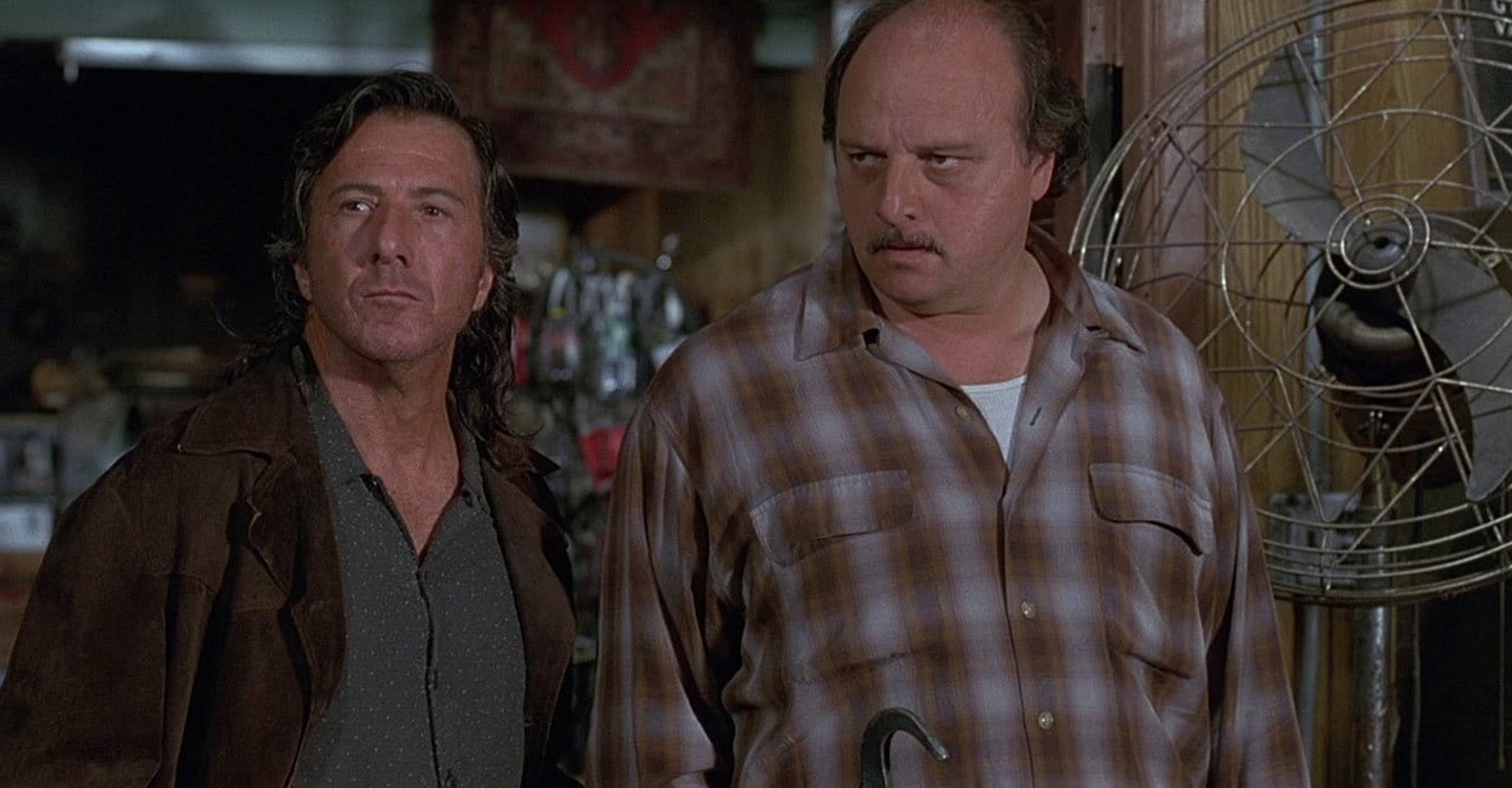 Image is from the film 'American Buffalo' (1996). Two middle ages men stand side by side, looking at something in the distance. They appear to be in a shop, and a fan stands behind them.