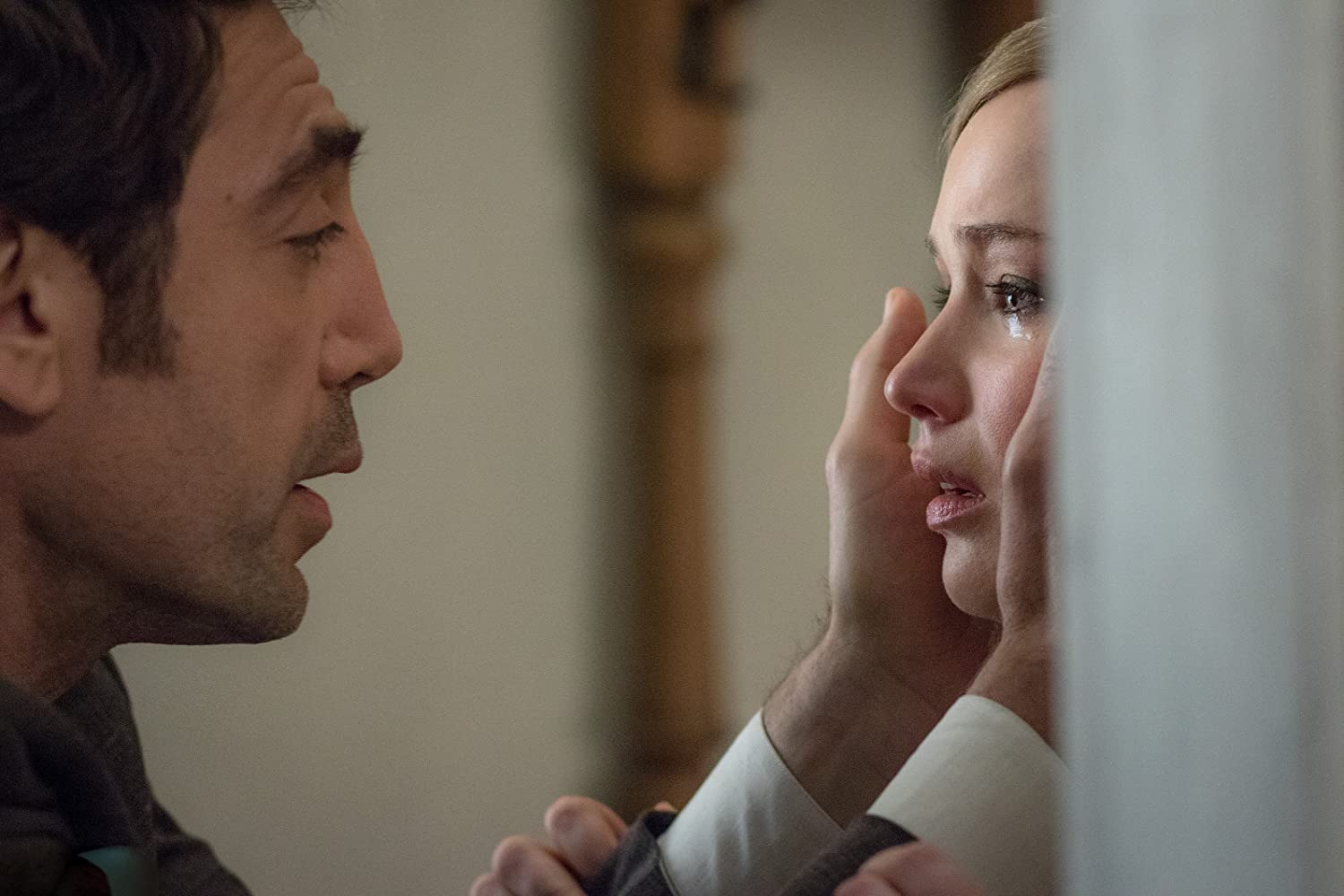 Javier Bardem as Him and Jennifer Lawrence as Mother in Mother! (2017). He holds her face, Mother is crying.
