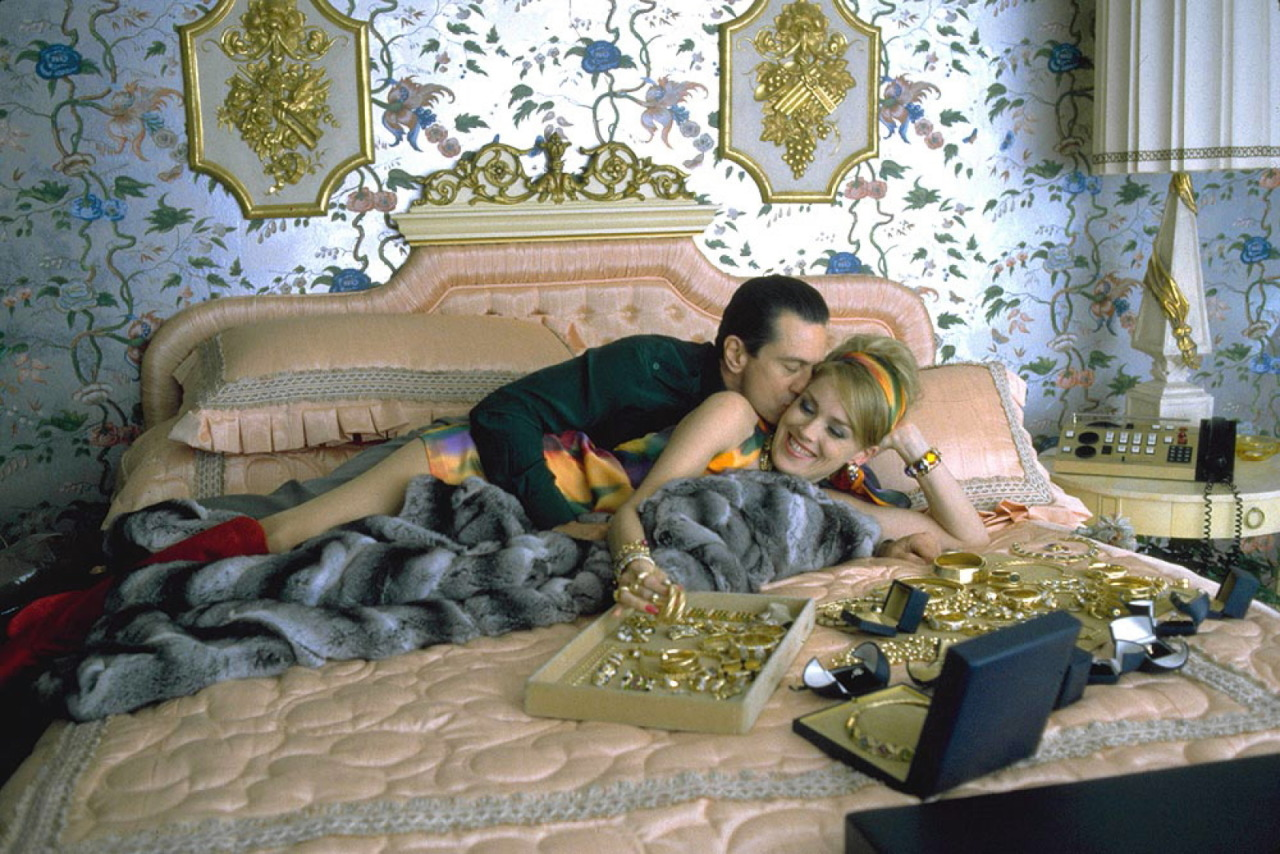 Robert De Niro and Sharon Stone in Casino (1995). Ace and Ginger are lying together in a pink double bed with a fur throw in an ornate bedroom with gold adorning the wall and furnishings. Ace is lying behind Ginder and embraces her, kissing the side of her head. Ginger, a slim blonde white lady in a multi-coloured shift dress with a matching headband, is smiling and reaching forwards to handle the huge pile of gold jewellery that is spread out in boxes on the bed.