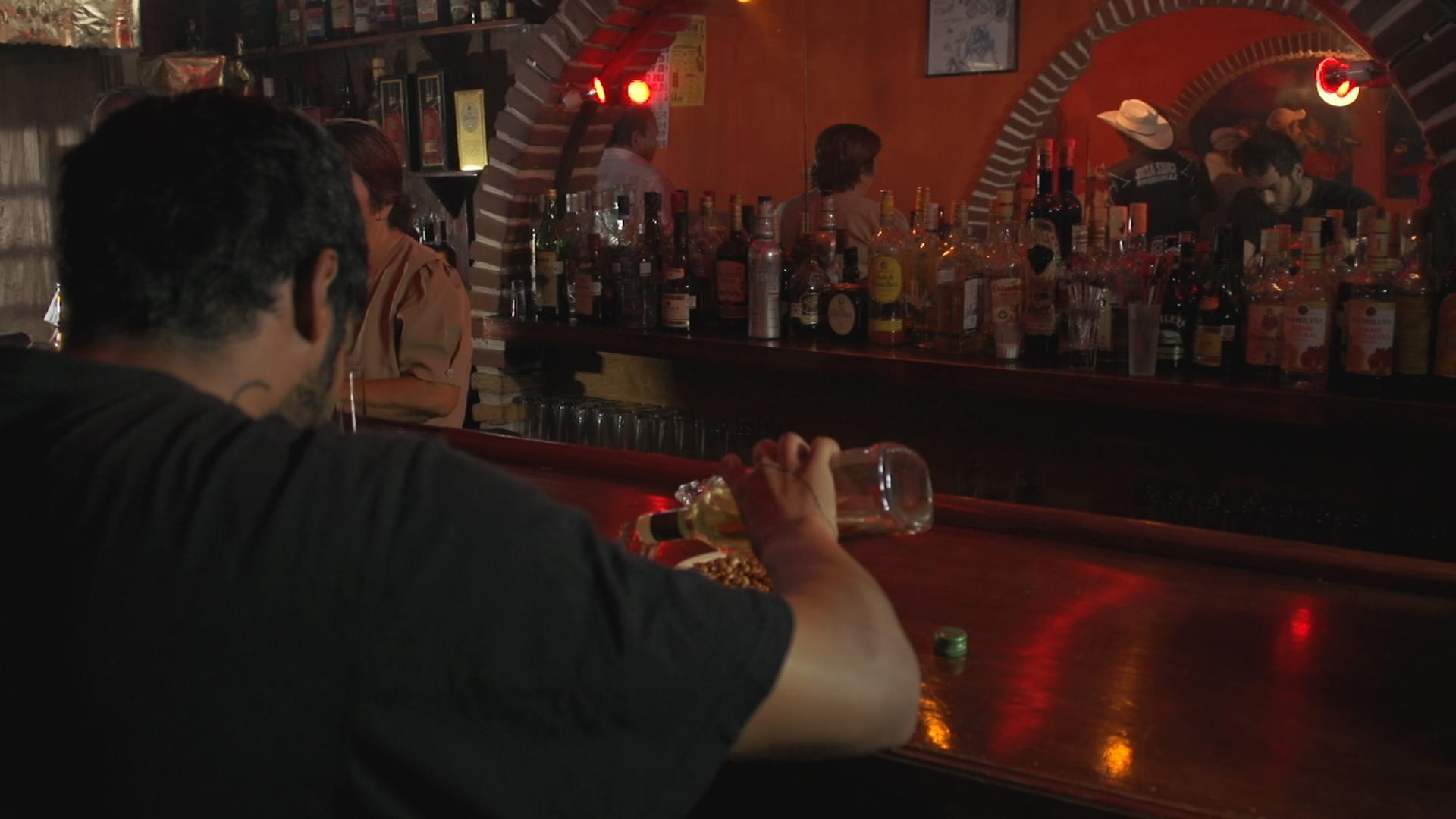 La imagen muestra al actor mexicano Hugo Catalán en la película Fuego Adentro dirigida por Jesús Mario Lozano en una cantina bebiendo tequila.