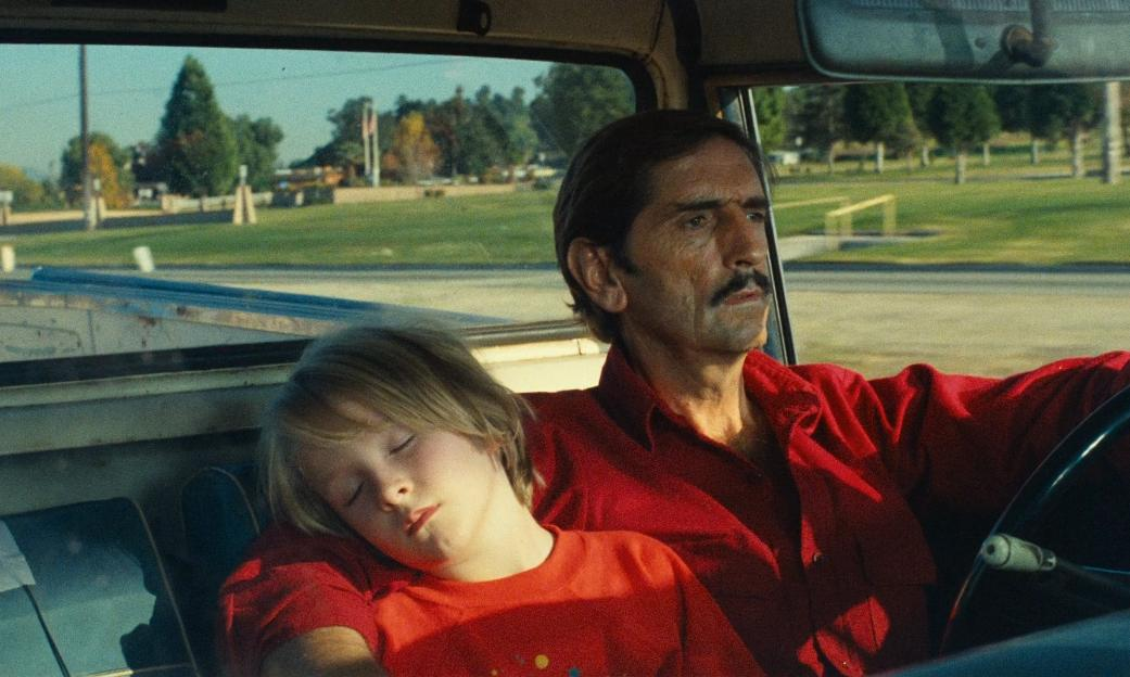 Harry Dean Stanton and Hunter Carson in Paris, Texas (1984). Travis, an older-looking white man with dark hair, a thin mustache, and a lined face with a pensive expression, is driving a car along a wide road with grass and trees in the background. A small blonde boy in a red t-shirt is sleeping soundly next to him, and Travis has an arm around him.