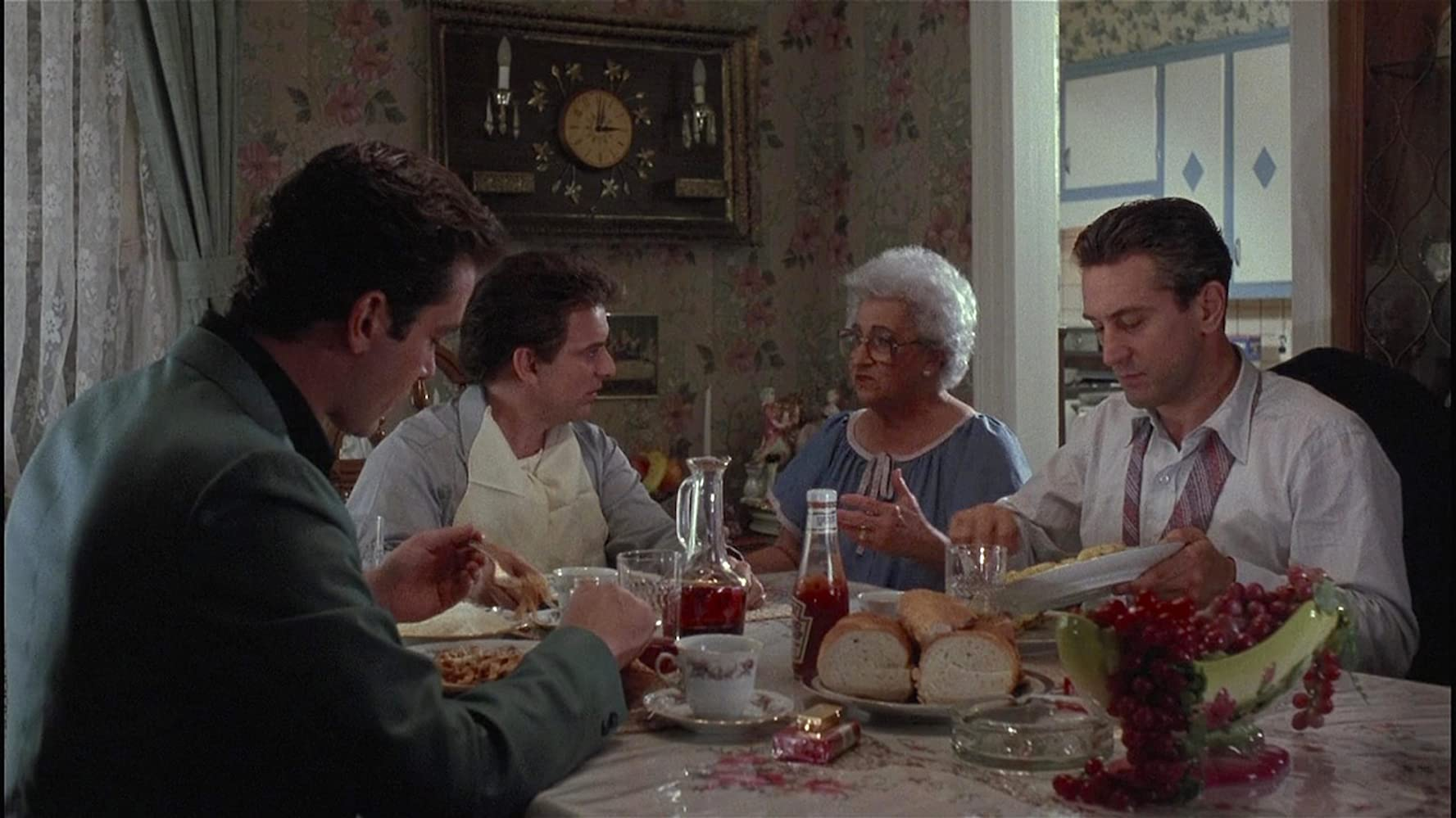Robert De Niro, Ray Liotta, Joe Pesci, and Catherine Scorsese in Goodfellas (1990). The four are sitting around a small dining table in a family home, an assortment of pasta, bread, fruit, and condiments filling the table. The three  Italian American men all wear dress shirts and have similarly cropped brown hair. Mrs DeVito (Scorsese) sits in the middle, she is an elderly woman with very curly short white hair and large 80s-style glasses, wearing a blue dress. She addresses the boys in conversation.