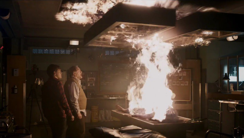 The Autopsy of Jane Doe (2016). Tommy and his son Austin, a young white man with brown hair, wearing a red plaid shirt, are standing in the darkened morgue. They are staring at the body of Jane Doe on the table, which has burst into flames which rise up to the ceiling.