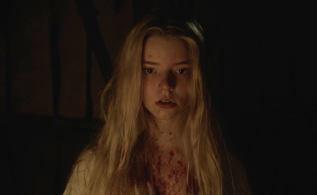 Anya Taylor-Joy as Thomasin in The Witch: A New-England Folktale (2015). Thomasin is covered in blood, she looks towards the camera, her expression is unclear.