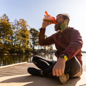 Man drinking protein drink on a dock