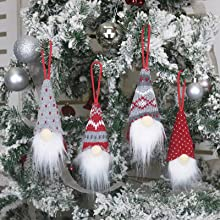 Four cute dwarf Santas of different colors hang on the Christmas tree