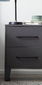 Closeup of gray, 2-drawer nightstand holding books and a lamp