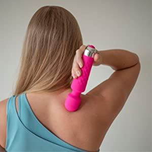 A girl using TheBoo massager on her shoulder