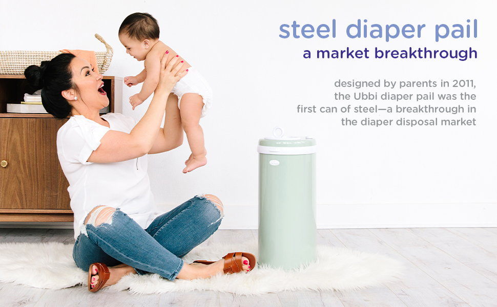 Picture of mom holding up baby and smiling next to sage Ubbi diaper pail