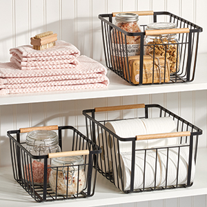 black wire baskets holding glass jars and toilet paper, towels on white shelves with white wood wall