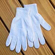 white knit cotton gloves on a wood background.