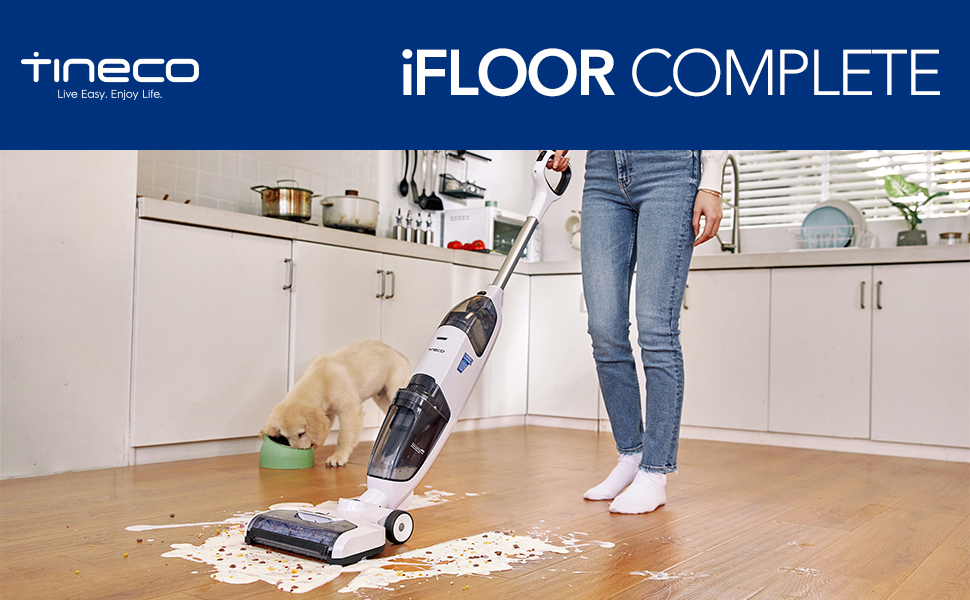 Woman using iFloor Complete in kitchen, dog eating behind her