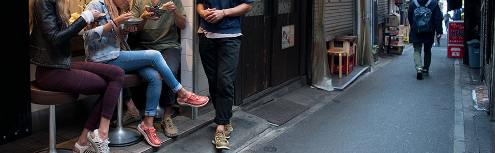 A group of friends sits at an outside cafe bar eating noodles from bowls and wearing sandals.