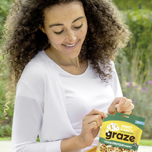 Een vrouw op een picnic kleedje vol met gezonde snacks en de zak van graze snack mix