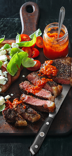A Kessaku Dynasty Series Steak Knife next to thick slices of steak, tomato, lettuce, and cheese.
