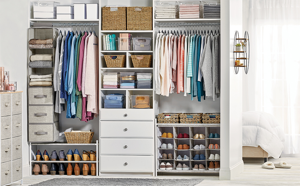 Cream fabric dressers, totes, clear bins, natural baskets, clothing in a white closet setting, bed