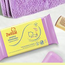 De verpakking van de Zwitsal Billendoekjes Sensitive met daarnaast een handdoekje en een kammetje