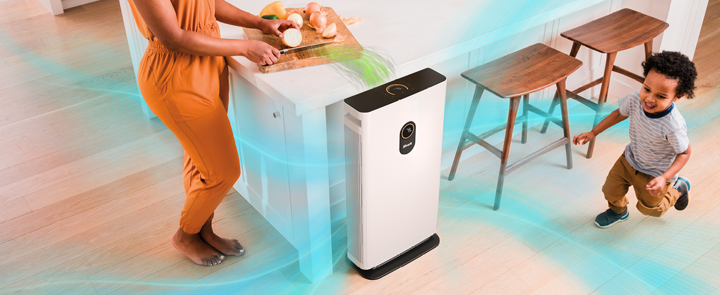 woman cutting onions in the kitchen and air purifier removing odors