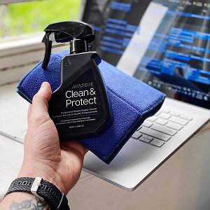 Hand holding spray bottle and cloth infront of laptop