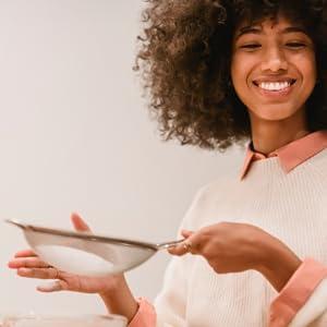 Femme souriante avec un tamis de farine de coco