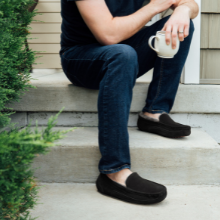 Man drinking coffee wearing moccasin