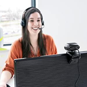 A woman smiling, look at the back of the webcam with a cable