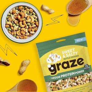 Een kommetje vol met de noten mix van graze en twee lepels met honing