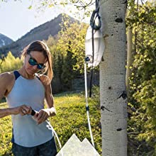 Woman standing with MSR Trail Base set up as a gravity system suspended from a tree